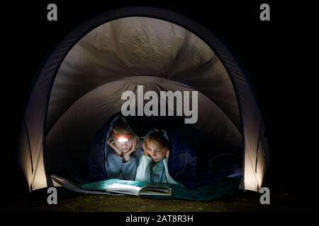 Preteen girls laying in a camping tent wrapped in a sleeping bag reading a book with flashlight at night during summer holidays - Stock Photo