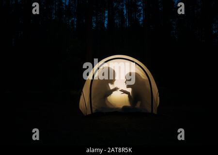 Silhouettes of children playing in camping tent at night making shadow puppets with flashlight enjoying summer holidays - Stock Photo