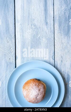 Single doughnut on two blue plates on a wooden table. Above view of just one german donut. Berliner doughnut with chocolate filling and powdered sugar - Stock Photo