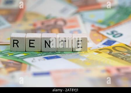 Cubes with letters with German word Rente, Pension, on banknotes - Stock Photo