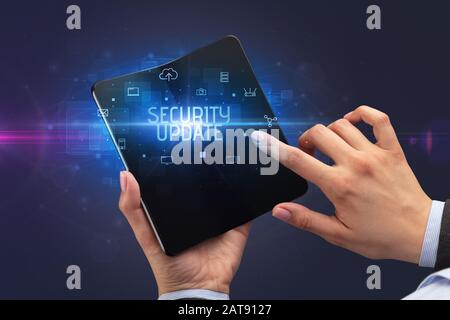 Businessman holding a foldable smartphone with SECURITY UPDATE inscription, cyber security concept