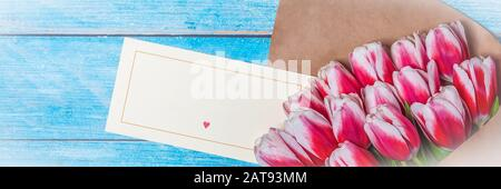 Bouquet of red tulips for the holiday women's day and valentine's day on the background of wooden boards - Stock Photo