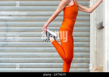 close up of a woman doing leg stretch warm up exercise, wearing orange sportswear.