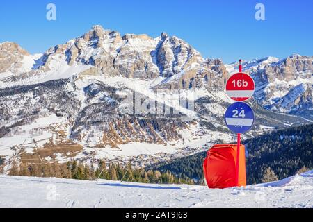 Winter view of Piz dles Cunturines (Cima Cunturines) from a ski slope in Alta Badia, South Tyrol, Dolomiti mountains, Italy, with piste signs for red - Stock Photo