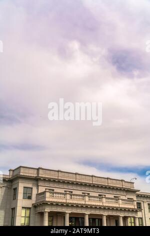 Cloudy blue sky over building with balcony and huge columns at the entrance - Stock Photo