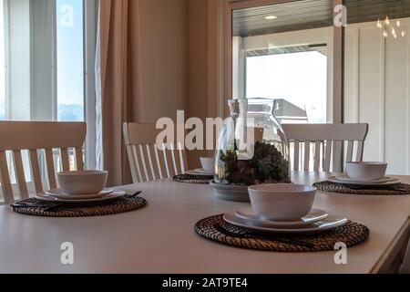 Table setting at the dining room of home against window and glass door. The decorative centerpiece is surrounded by tableware on placemats. - Stock Photo