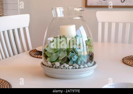 Ornamental glass jar with plants and candle on the dining table of home. White chairs, tableware, and placemats can be seen around the centerpiece. - Stock Photo