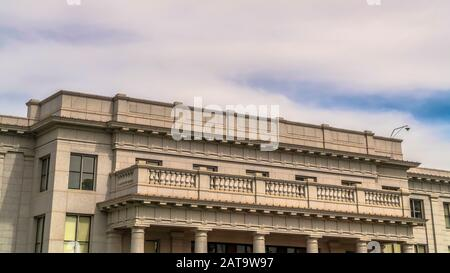 Panorama Cloudy blue sky over building with balcony and huge columns at the entrance - Stock Photo