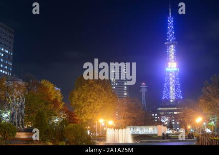 Sapporo, Japan - October 30, 2019: Sapporo TV Tower shines like a blue beacon in Odori Park on a chilly autumn night - Stock Photo