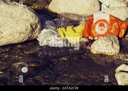 pollution concept with plastic bottles and plastic bags on the riverbank - Stock Photo