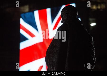 London, UK. 31 January, 2020. A statue of Gandhi in Parliament Square is silhouetted against a Union Jack appearing on a screen used for a Leave Means Leave rally on the evening on which the UK leaves the European Union. Credit: Mark Kerrison/Alamy Live News - Stock Photo