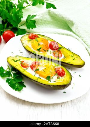 Scrambled eggs with cherry tomatoes in two halves of avocado in a plate, napkin and fork on a wooden board background - Stock Photo