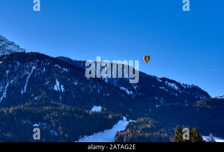 A hot air balloon flies over the ski slopes of the Dobbiaco valley - Stock Photo