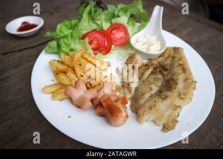 fish steak , grilled fish or catfish steak with French fries and salad - Stock Photo