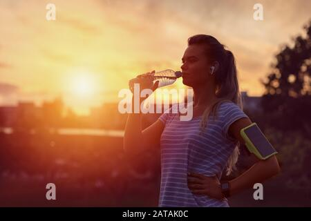 Modern sporty woman drinking water in park at dawn after intense jogging workout - Stock Photo