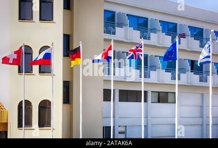 Switzerland, Russian, Netherlands, German, British, Greek, European Union Flags on flagpoles fluttering in the wind opposite the hotel - Stock Photo