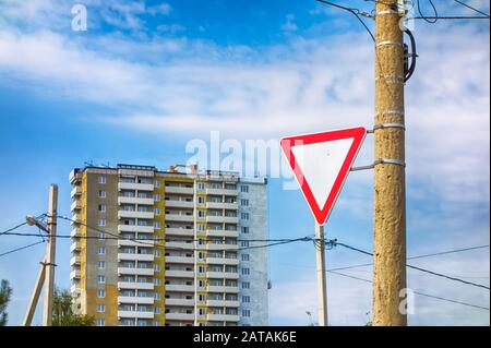 Give way road sign on pillar against multi-storey building and cloudy sky. - Stock Photo