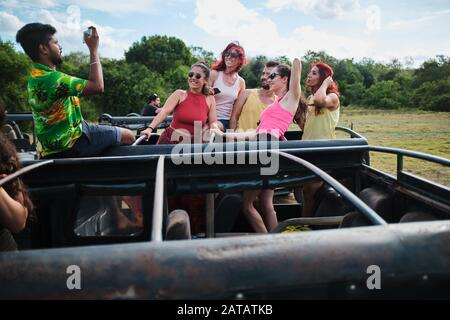 White tourist photographing with their smart phones during elephant safari in Minneriya national park in Sri Lanka. - Stock Photo