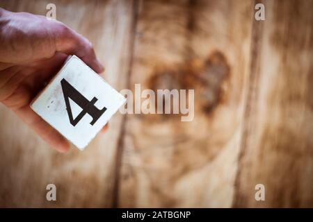Number 4 - a hand holding a white block with number four over vintage wooden table - Stock Photo