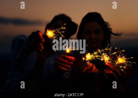 Shot of a young people playing with sparklers at night. Best friends hanging out at night - Stock Photo