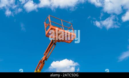 Cherry picker on blue sky background. Boom with lift bucket of heavy machinery. Orange platform of the telescopic construction lift in summer. - Stock Photo
