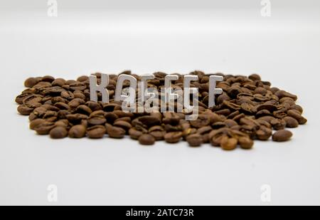 Kaffee written in wooden letters and coffee beans isolated on white background - Stock Photo