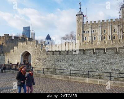 2 young people walking past the Tower of London with the city's financial district on the skyline - Stock Photo