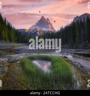 Hot air balloons flying over Dolomites at sunset, Auronzo di Cadore, Belluno, Veneto, Italy Stock Photo