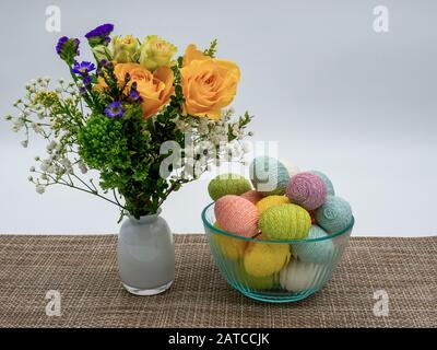 Flower arrangement in a white case with a glass bowl of decorated pastel colorful Easter eggs on top of a beige patterned table runner with a white ba - Stock Photo