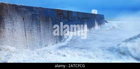 A harbor wall with a rough stormy sea crashing against the wall causing the sea to be blurred and in motion, waves are crashing over the wall, there i - Stock Photo