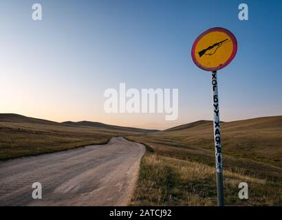 Dirt road in Hustai or Khustain Nuruu National Park nature reserve with no rifle shooting warning sign at sunrise, Tov Province, Mongolia, Asia - Stock Photo