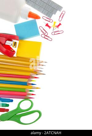 School supplies, pencils scissors, sticky notes, stapler, staples, glue, paper clips and tacks on a white background. - Stock Photo