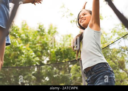 Little girls jumping and playing on a trampoline. - Stock Photo