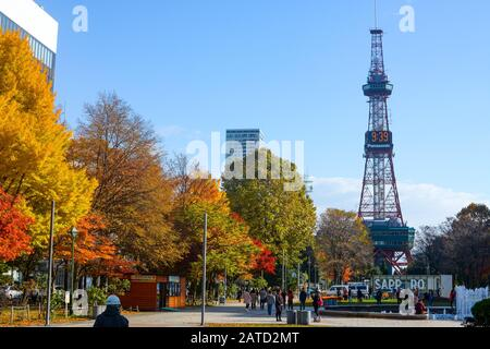 Sapporo, Japan - October 31, 2019: Crowds enjoy sunshine on a chilly autumn day in front of the Sapporo TV Tower in Odori Park - Stock Photo