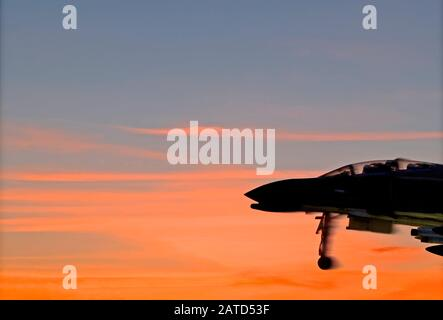 Silhouette of a historic McDonnell Douglas F-4 Phantom II fighter jet taking off against the red clouds of the morning sky over Mobile Bay, Alabama. - Stock Photo