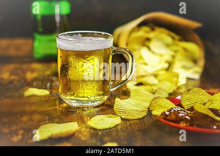 A glass of cold beer and chips on a wooden table. The concept of a football fan - Stock Photo