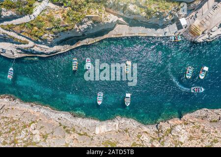 Narrow bay with pleasure boats among the rocks, aerial view - Stock Photo