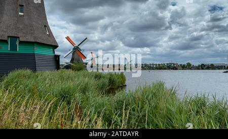 Traditional Windmills along river Zaan, Zaanse Schans, Zaandam, North Holland, Netherlands - Stock Photo