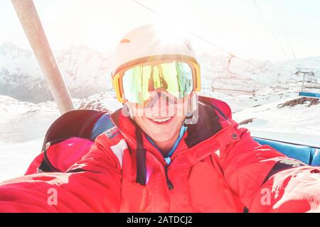 Happy skier taking selfie photo with smartphone camera sitting on ski lift - Young man having fun in winter snow resort vacation with back light - Spo - Stock Photo