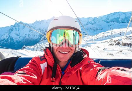 Happy snowboarder taking selfie photo with smartphone camera sitting on ski lift - Young man having fun in winter snow resort vacation - Extreme sport - Stock Photo