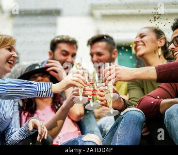 Happy friends cheering with champagne and making party outdoor - Young students celebrating drinking and laughing - Loud fest loud,concept - Main focu - Stock Photo