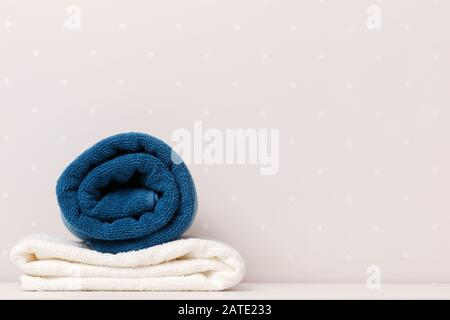 Close-up of towels blue and white color lay on a table against the background of light walls. - Stock Photo