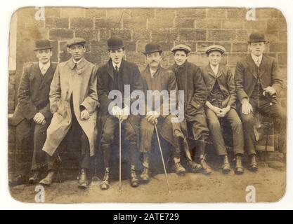 Early 1900's Edwardian cabinet card of group of seven young men and boys wearing flat caps and bowler hats, some holding walking sticks or canes, rounded collars, sitting together resting after a walk on a bench, U.K. Circa 1905 - Stock Photo