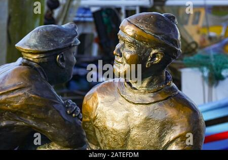 The bronze figurs honors the work of the fishermen. It is located in Neuharlingersiel / North Sea /Germany. - Stock Photo