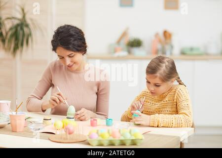 Candid portrait of mother and daughter painting Easter eggs pastel colors sitting at table in cozy kitchen interior, copy space - Stock Photo