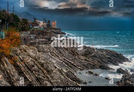 Interesting rock formations on the coast at Nervi, Italy with a view along the coastline to the town perched above the ocean in evening light - Stock Photo