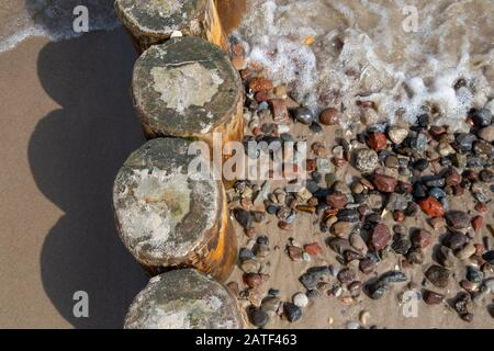 groynes with washed stones on the beach of the Baltic Sea in the seaside resort Zempin on Usedom - Stock Photo