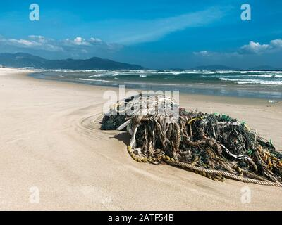 Discarded garbage on the shore of a beautiful sandy beach, sea waves. Plastic, bottles, environmental pollution bags. Ecological problem. Sea shore wi - Stock Photo