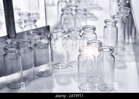 Empty bottles in the processing machine in pharmaceutical plant - Stock Photo