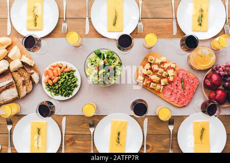 Vegetables and fruits on the festive table. Festive table set for six people. Wooden background top view mock-up - Stock Photo